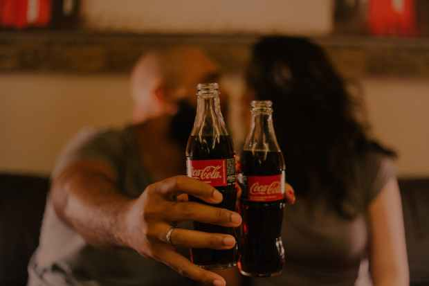 close up photography of people holding coca cola bottles